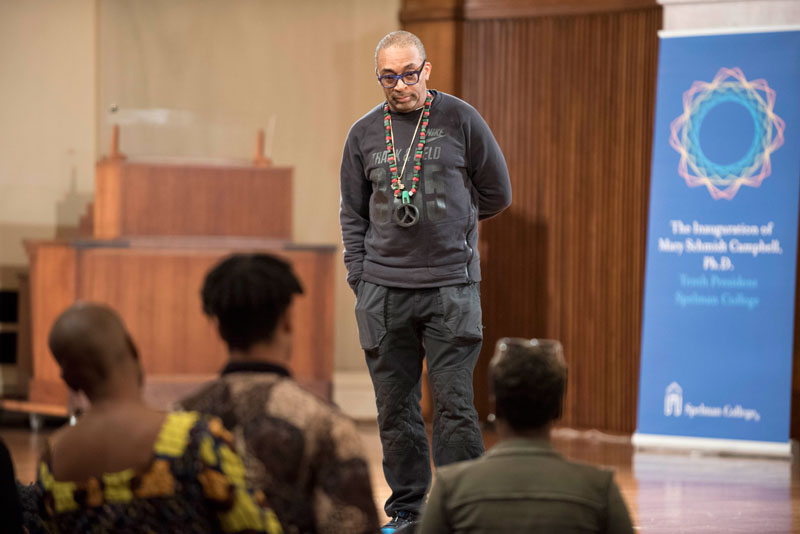 Spike Lee giving a talk at Spelman College in front of event graphics designed by Drew Sisk